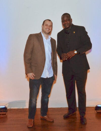 two men in a tan coat and black coat at the Race 4 Achievement event.